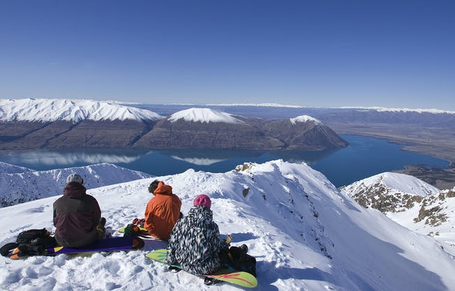 Three people sitting on their snowboards on top of Mount Ohau gaze out at the view of the lake below and the Southern Alps during a break on their NZ snow tour